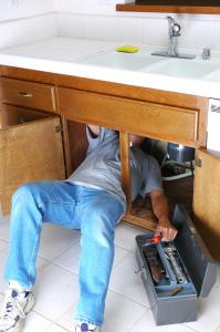 one of our plumbers in Santa Clara CA is under the sink fixing a broken garbage disposal