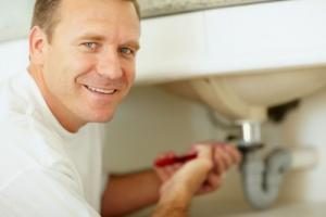 a Santa Clara Plumbing pro tightens a leaky sink drain with a pipe wrench
